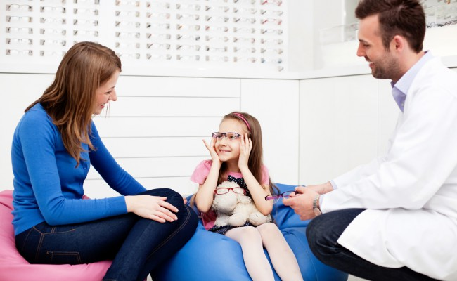 Mother visits optician, optometrist with child
